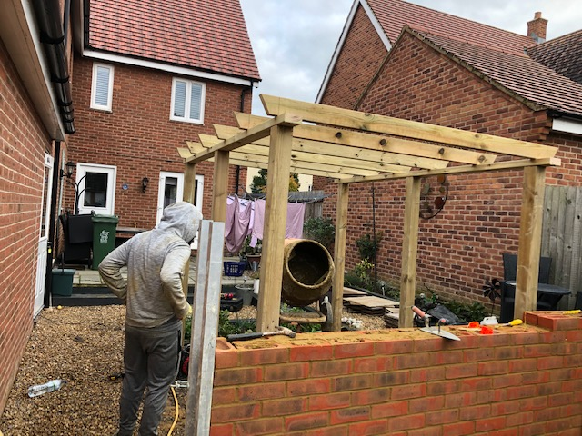 Brick wall and garden pergola being built